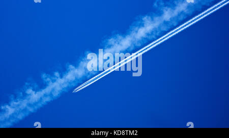Contrail clouds from aircraft passing over the mountain exclave quadripoint border village of Jungholz, Tirol, Austria. - Stock Photo