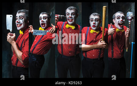 The scary clown holding a knife on dack. Halloween concept - Stock Photo