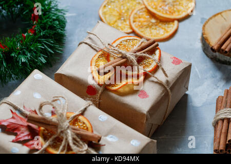 View of christmas gift boxes in a kraft paper decorated dried orange slices, cinnamon sticks and a leaf of a tree. - Stock Photo