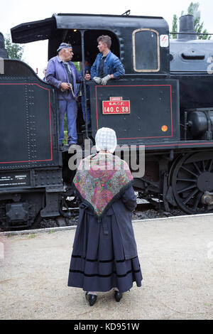 EYMOUTIERS, FRANCE - JUNE 27, 2017: The Limoges - Eymoutiers steam train line. Older woman in traditional 1950s - Stock Photo