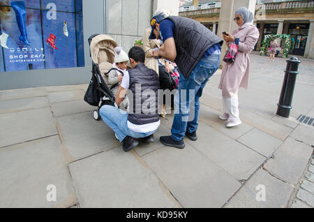 London, England, UK. Muslim family in Covent Garden - men looking after the children - Stock Photo