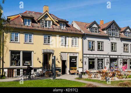 Street cafe and wooden Norwegian buildings with people outside enjoying sunshine in city centre in summer. Tromso, - Stock Photo