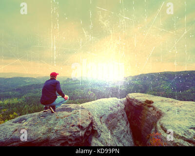 Lens defect. Hiker man stays on a rocky ridge and enjoy view over long valley to horizon. Cold Sun hidden in clouds. - Stock Photo