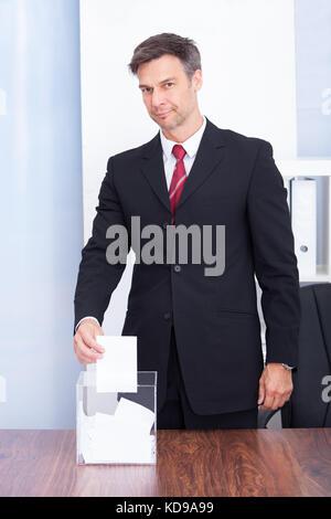 Happy Mature Businessman Inserting Ballot In Transparent Box - Stock Photo
