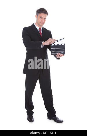 Portrait Of Mature Businessman Holding Clapperboard Over White Background - Stock Photo
