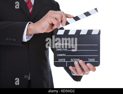 Close-up Of A Businessman Holding Clapperboard Over White Background - Stock Photo