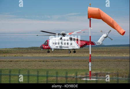 Coastguard search and rescue helicopter taking off from Caernarfon airport with a wind sock in the foreground. - Stock Photo