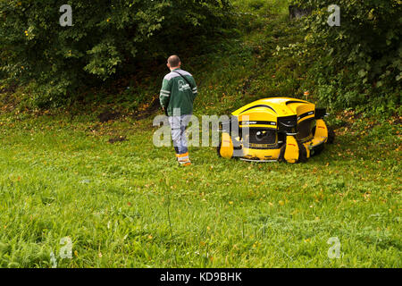 public park maintenance may with robotic lawnmower - Stock Photo