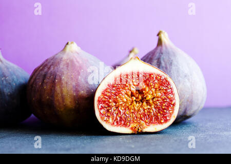 Colorfull still life organic ripe figs on stony table, beautiful purple violet background. Selective focus on sliced - Stock Photo