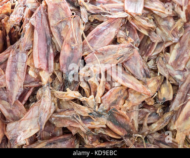 Dried squid pile for sale in the local market near the sea in the eastern of Thailand. - Stock Photo