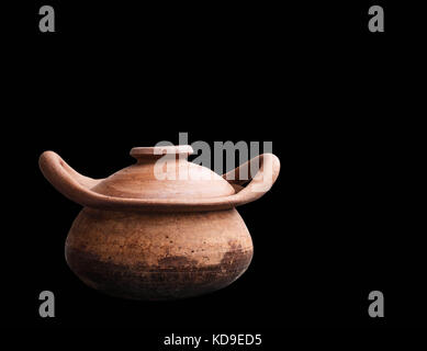 Old clay pot on a black background. - Stock Photo
