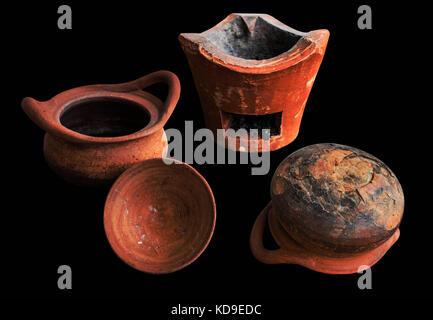 Old clay pot and charcoal on black background. - Stock Photo