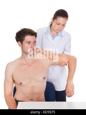 Orthopedic Surgeon Examining Patients Hand On White Background - Stock Photo