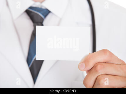 Closeup photo of doctor hand showing empty visiting card - Stock Photo