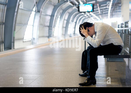 Train delay or problem in the train station, tired desperate Aisan passenger waiting in the terminal with suitcase. - Stock Photo