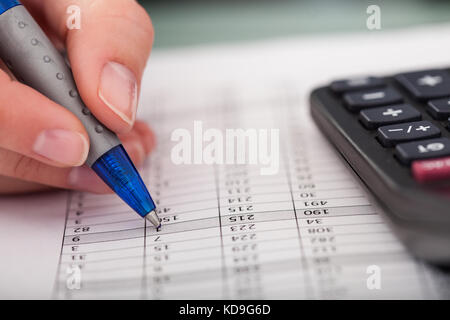 Close-up Of Hand Holding Pen With Calculator - Stock Photo