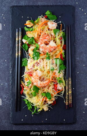 Noodles with prawns and vegetables on a black stone plate on a grey abstract background. Healthy food concept - Stock Photo