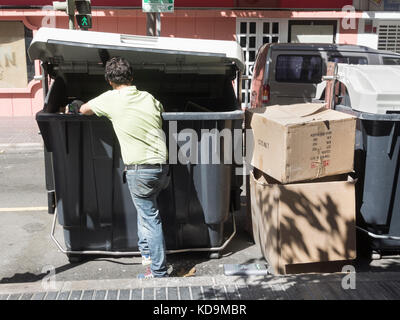 Man looking for food in rubbish containers in street in Spain - Stock Photo