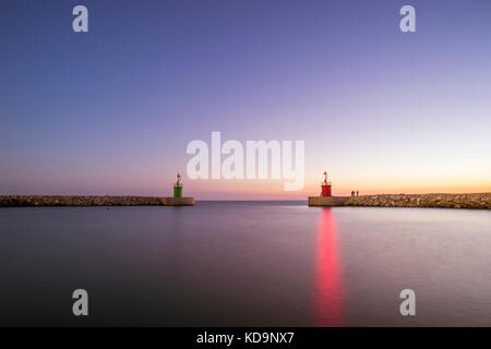 Seascape of two small lighthouse with their reflections on the sea at sunset. Some people are fishing under the - Stock Photo