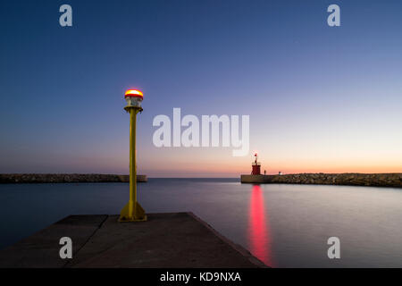 Seascape of a small lighthouse with his red reflections on the sea at sunset. Some people are fishing under the - Stock Photo