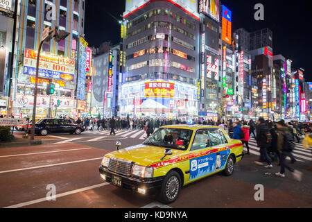 TOKYO - DECEMBER 31, 2016: A taxi driver is waiting for a passenger in Shinjuko district in Tokyo at night. December - Stock Photo