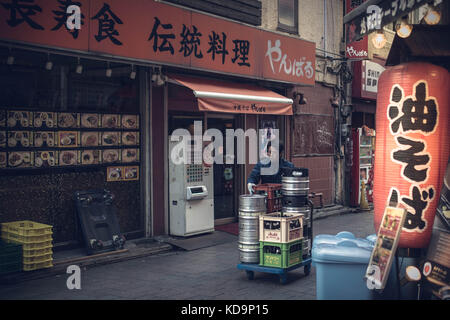 TOKYO - JAPAN - JANUARY 4, 2017. A worker is carrying barrels in a restaurant in Shinjuku district. Shinjuku is - Stock Photo