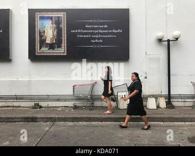Bangkok, Thailand. 11th Oct, 2017. Two Thais dressed in black walking past a poster featuring Thailand's deceased - Stock Photo