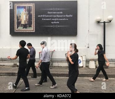 Bangkok, Thailand. 11th Oct, 2017. Thais dressed in black walking past a poster featuring Thailand's deceased King - Stock Photo