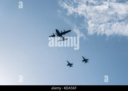 Madrid, Spain - October 12, 2017: Hercules KC-130 tanker aircraft refuelling in flight  two jet fighters in Spanish - Stock Photo