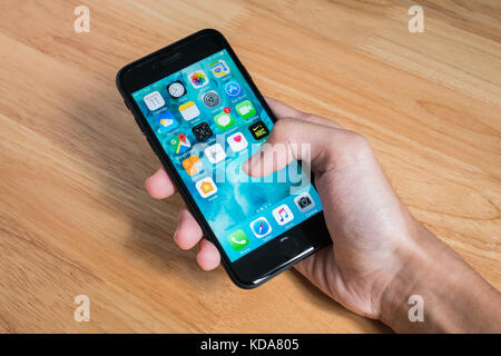 Bangkok, Thailand - October 11, 2017 : Apple iPhone 7 held in one hand showing its screen with Home Screen. - Stock Photo