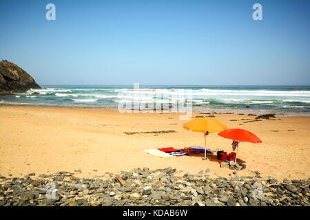 Beach umbrellas in the sand at beach Praia do Vale dos Homens near Aljezur, Algarve Portugal - Stock Photo