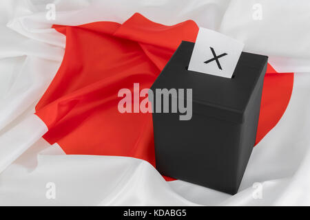 Japanese 'Circle of the Sun' / 'Rising Sun' flag with black ballot box - as metaphor for Japanese General Election. - Stock Photo