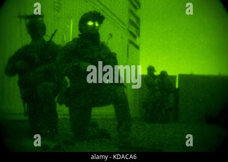 U.S. Marine Corps soldiers provide security through night vision goggles during visit, board, search and seizure - Stock Photo