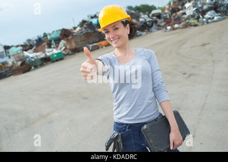 female worker car scrap yard - Stock Photo