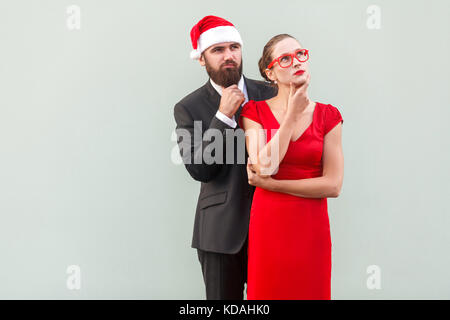 Well dressed businessman and woman looking away, touching chin and thinking. Studio shot - Stock Photo
