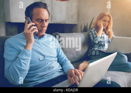 Mature couple busy working from home - Stock Photo