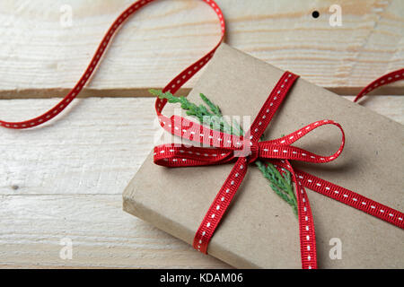 Gift box, wrapped in recycled paper and red bow on wood background - Stock Photo