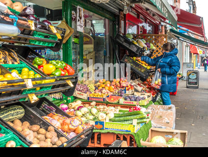 Customer choosing apples from a grocer's shop, with fruit and vegetables outside, on the main road in South Ealing, - Stock Photo