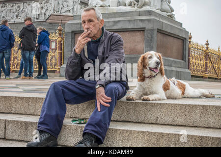 Old / elderly man sitting on steps of the Albert Memorial, smoking a cigarette, his dog lying next to him. Kensington - Stock Photo