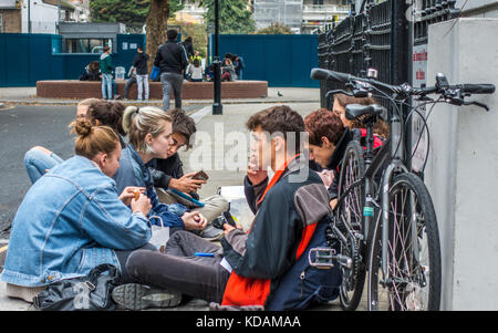 A gathering of teenage college students - one of them smoking a cigarette - sitting in a group on the pavement, - Stock Photo