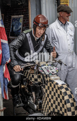 Actor playing the part of George Formby on a recreation of the Shuttleworth Speed Demon in the film 'No Limit'. - Stock Photo