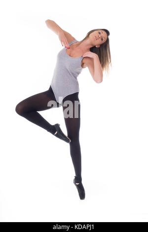 young beautiful woman dancer with long black hair wearing gray vest and tights jumping on a light white studio background - Stock Photo