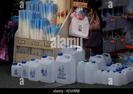 water cans and candles on sale at Lourdes, france - Stock Photo