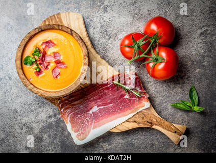 Spanish tomato soup Salmorejo served in olive wooden bowl with ham jamon serrano on stone background. Top view. - Stock Photo