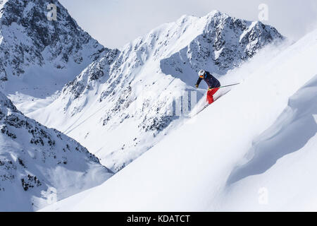 Extreme skier going through steep slope - Stock Photo