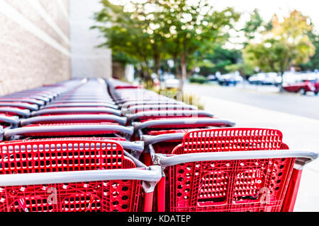 Many rows of red shopping carts outside by store with closeup by parking lot - Stock Photo