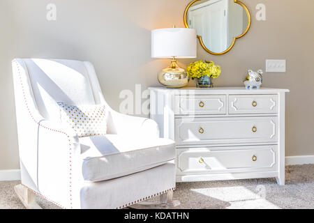 Bright white modern rocking chair in nursery room with chest of drawers, decorations in model staging home, apartment - Stock Photo