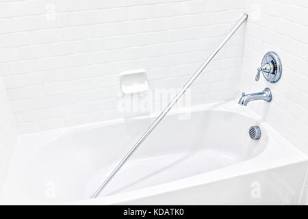 Closeup of new unfinished white modern tiled shower with bathtub bath and pole rod in tub - Stock Photo