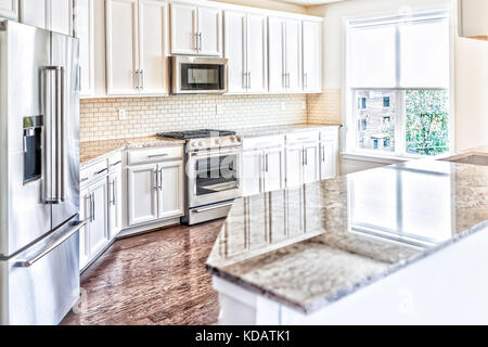 Modern gray, brown kitchen features front cabinets with granite countertops and tile backsplash with island and - Stock Photo