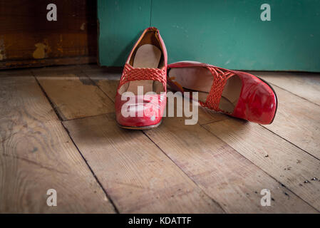 Worn red women's dress shoes on wooden floor - Stock Photo